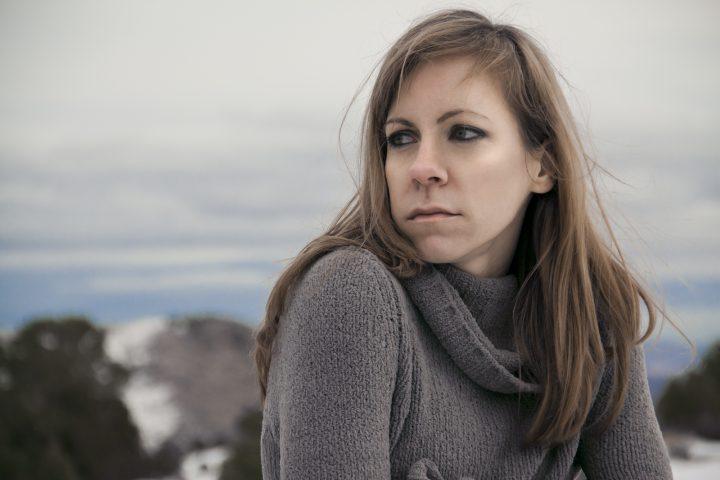 A sad, lonely brunette gazing over shoulder at beautiful snow la