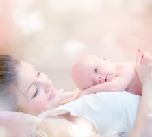 Mother and her Newborn Baby. Happy Mother and Baby kissing and hugging. Resting in bed together. High key soft image of Beautiful Family. Maternity concept. Parenthood. Motherhood