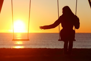 Single or divorced woman alone missing a boyfriend while swinging on the beach at sunset