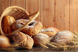 Whole grain wheat bread in basket with wheat ears.