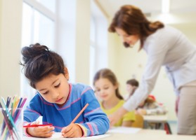 education, elementary school, children, creativity and people concept - happy little girl drawing with coloring pencils over classro