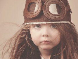 A little girl is wearing a pilot hat with goggles with an antique concept for career or imagination message.