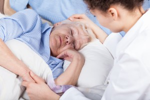 Woman caring about elderly lady in bed