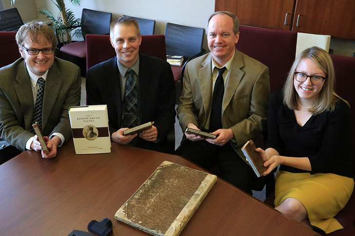 General Editor, Matthew J. Grow, Volume editors Brent M. Rogers, Alex D. Smith, and Production Editor Alison Palmer each hold a copy of the journals Willard Richards wrote in for Joseph Smith.