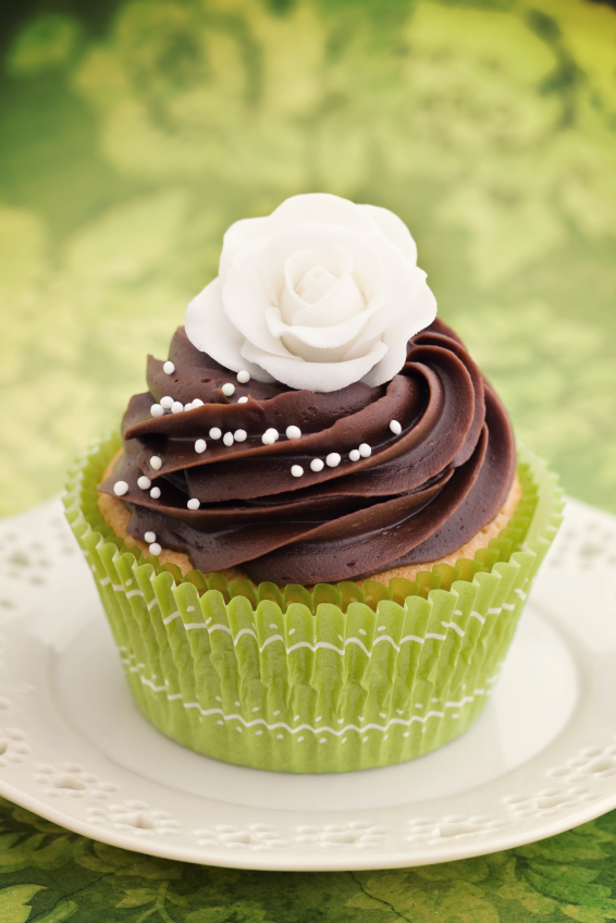 Cupcake decorated with chocolate frosting and a sugar rose