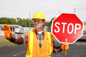 a construction worker holding a stop sign and directing traffic.
