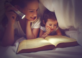 Family reading bedtime. Mom and child daughter reading a book with a flashlight under the blanket in bed