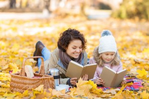 Nice weekend. Pleasant smiling glad mother and daughter enjoying reading books and lying on the blanket while spending great time in park