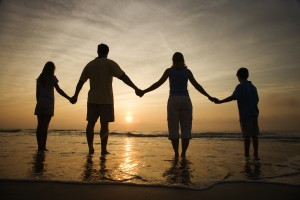 Silhouette of family holding hands on beach watching the sunset. Horizontally framed shot.