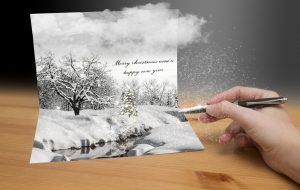 Snowy christmas card on the table and a hand with pen