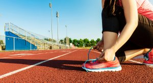 Female runner lacing her sneakers on a stadium running track