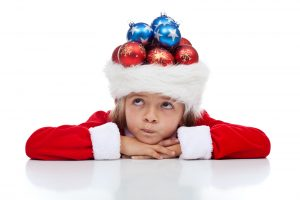 Wondering about my christmas presents - little girl with holidays related thoughts isolated