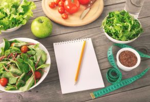 Blank notebook with various salad leaves and apple glass of water flax seed and measuring tape. Healthy eating weight loss and diet concept top view