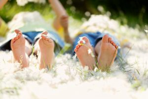 Happy little children lying in the grass with feathers barefoot playing happily childhood happiness concept