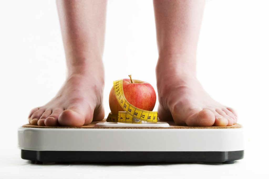 a pair of female feet standing on a bathroom scale with an apple and tape measure between them.