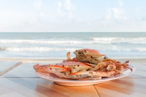 Steamed crab in plate with sea background