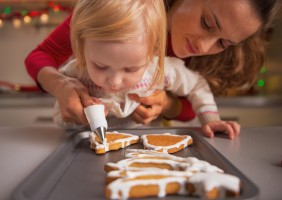 Baby Helping Mother Decorate Homemade Christmas Cookies With Gla