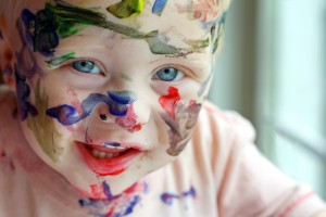 a close up photo of a baby boy who has covered his entire face in rainbow colored paint ** Note: Slight blurriness, best at smaller sizes