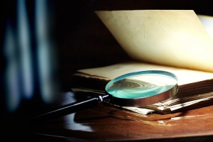 Old book and magnifier glass on a dark background as a symbol of knowledge and science ** Note: Shallow depth of field