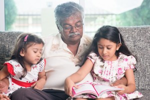 Grandparent and grandchildren reading story book. Happy Indian family at home. Asian grandfather and granddaughters indoor lifestyle.