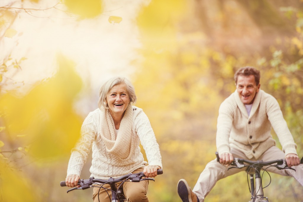 Active seniors ridding bike in autumn nature. They having fun outdoor. ** Note: Shallow depth of field