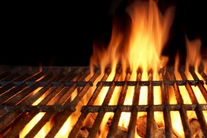 Empty Flaming Charcoal Grill With Flames Of Fire On Black Background Closeup. Summer Outdoor Barbeque Party or Picnic Concept.