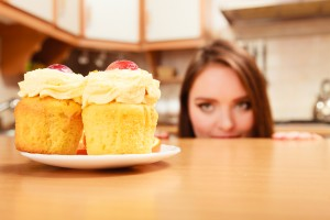Woman hiding behind table sneaking and looking at delicious cake with sweet cream and fruits on top. Appetite and gluttony concept.