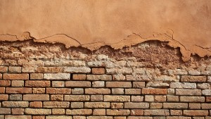 Photo closeup outdoor aged terracotta clay brick and decorative stucco facade wall exterior building materials for masonry construction on mural background horizontal picture
