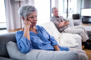 Upset senior couple ignoring each other at home